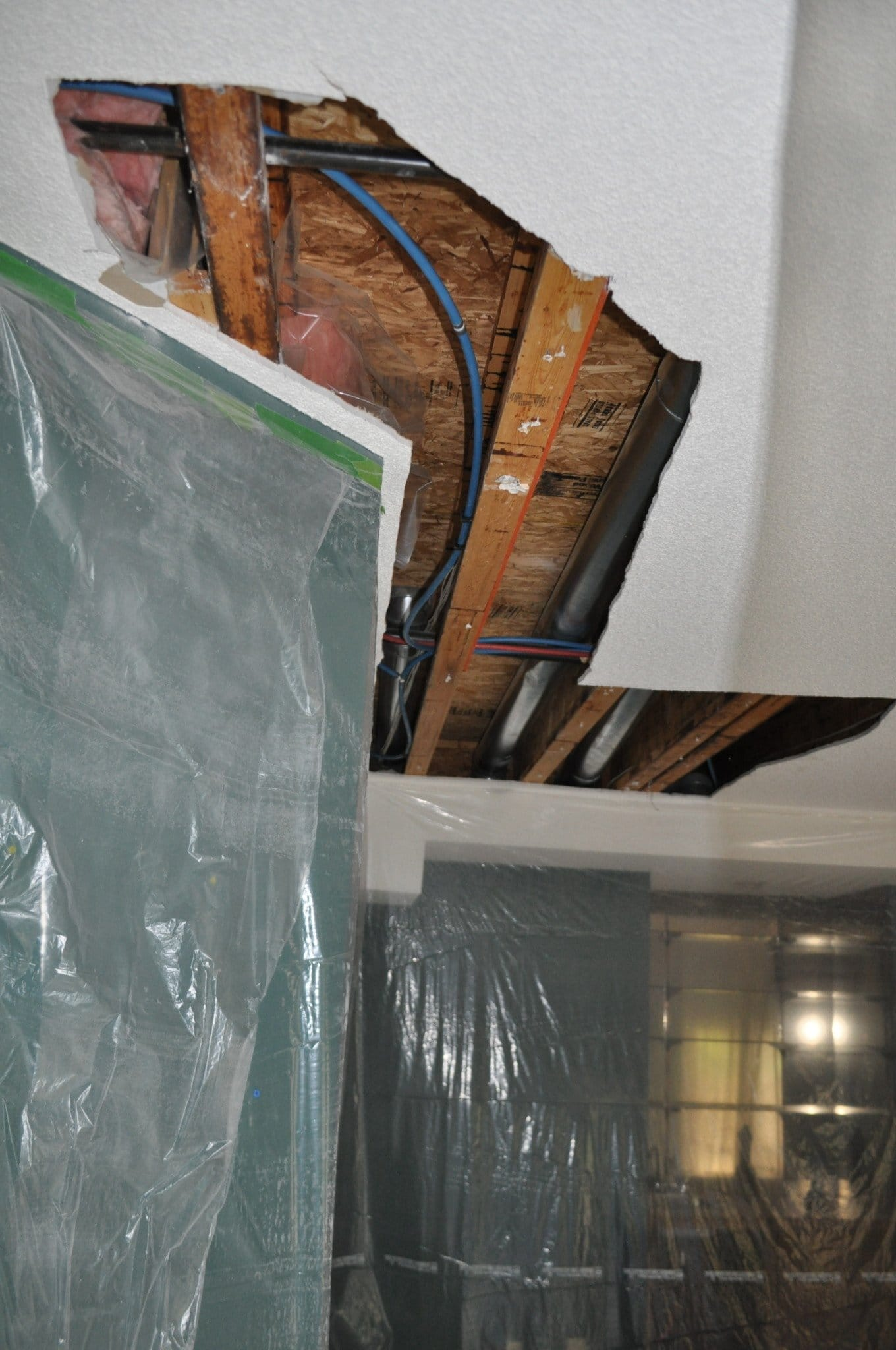 Holes are cut into the ceiling to remove the poly b piping from the customers home and replace with pex piping.